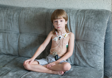 child with holter monitor sitting on couch