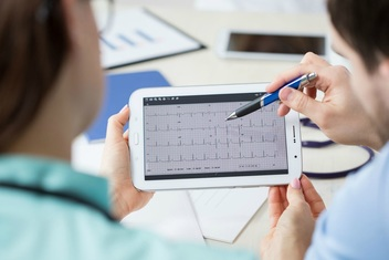 medical professional reviewing results on tablet computer