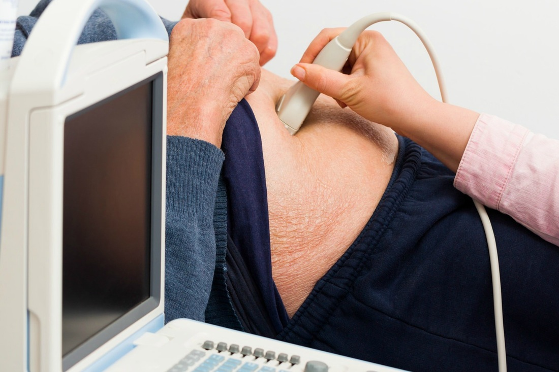 man being given ultrasound to stomach